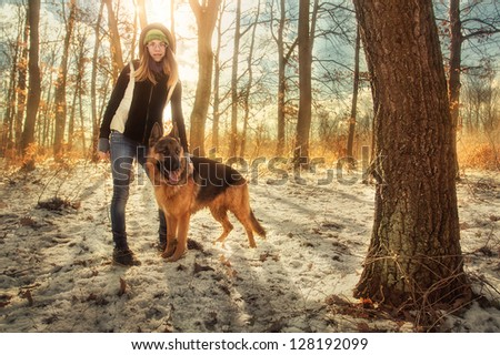 Girl and German shepherd at forest