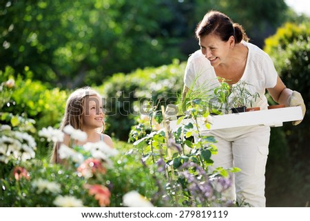 Girl and granny planting herbs in garden