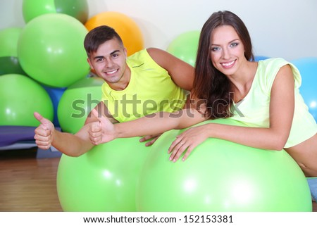 Girl and guy in fitness room - stock photo