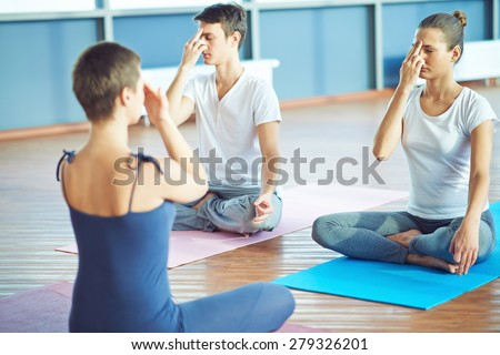 Girl and guy repeating yoga exercise after their teacher in gym - stock photo