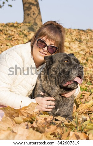 Girl and her Cane Corso dog enjoying sunny autumn day in the park - stock photo