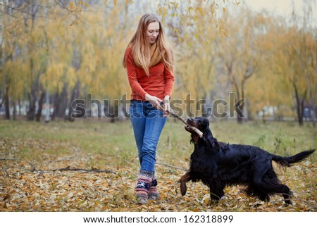 girl and her dog playing in the autumn park - stock photo