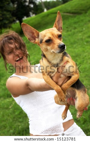 girl and her doggy on green grass background; focus on dog