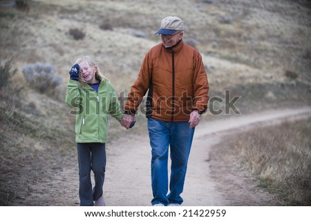 Girl and her grandfather holding hands on a walk