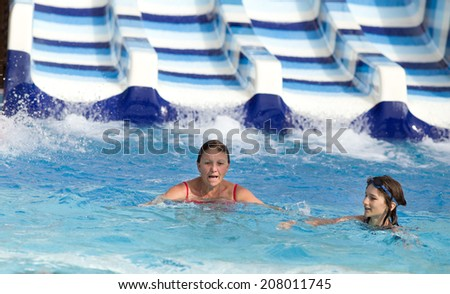 Girl and her grandmother swimming in pool in water park with toboggan in background - stock photo
