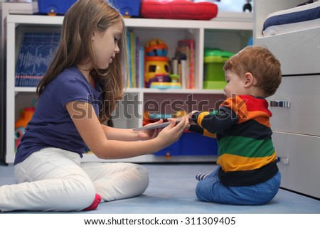 girl and her little brother arguing with a digital tablet computer - stock photo