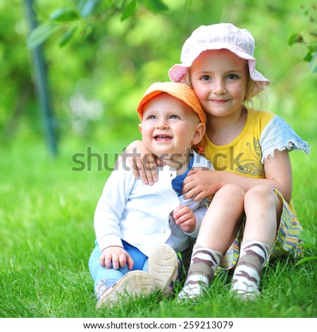 girl and her little brother sitting on  grass