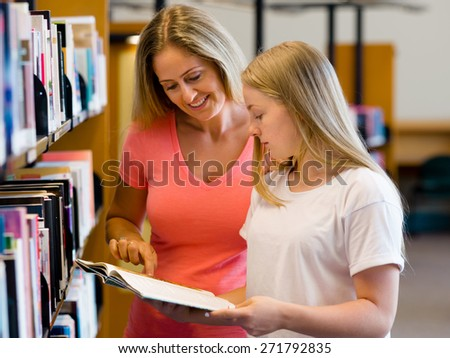 Girl and her mother in library choosing books - stock photo