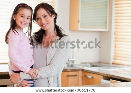 Girl and her mother posing in a kitchen - stock photo