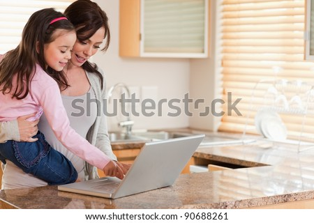 Girl and her mother using a laptop in a kitchen - stock photo