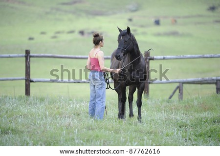 girl and horse in paddock - stock photo