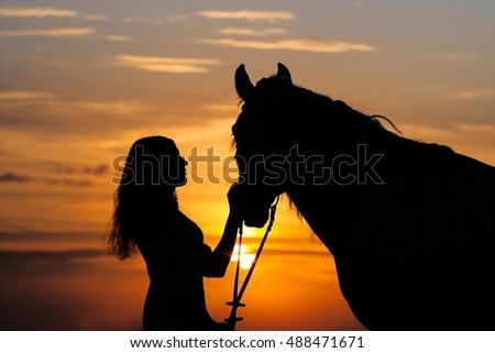 Girl and horse silhoutte at sunset
