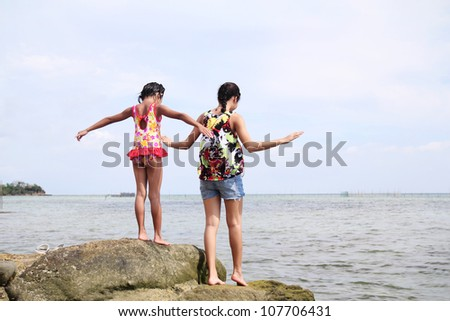 Girl and lady walking and looking down at the sea. - stock photo