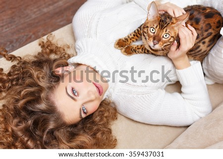 Girl and leopard cat home. Home comfort. Girl and a cat lying on the sofa. - stock photo