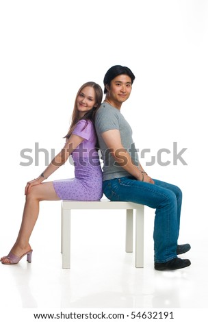 Girl and man is sitting back to back on small white table.
