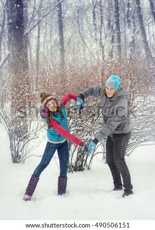 Girl and man play in the snow