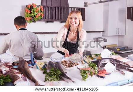 girl and man selling fish at the store