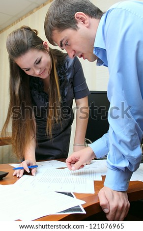 Girl and man working together in the office with papers