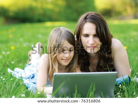 Girl and mommy working on notebook computer - stock photo
