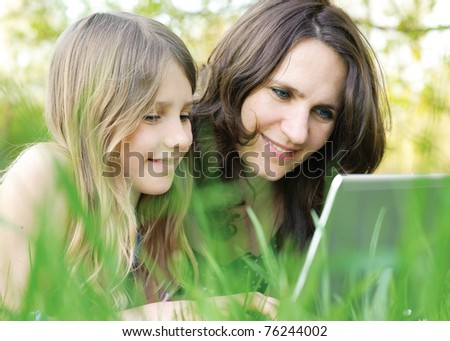 Girl and mommy working on notebook computer outdoor - stock photo