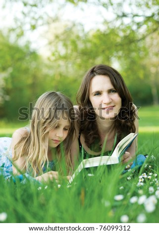 Girl and mother reading the book - stock photo