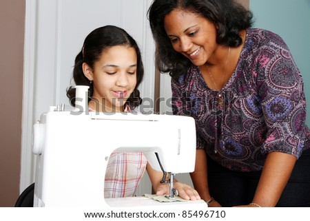 Girl and mother using a sewing machine to make crafts - stock photo