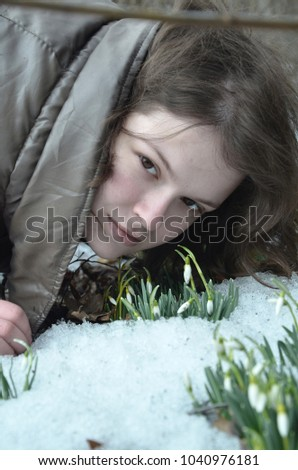 girl and snowdrops made their way through the snow