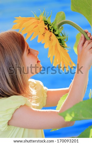 Girl and sunflower - beautiful girl is smelling sunflower in the garden