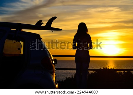 girl and surfboard silhouettes at sunset - stock photo