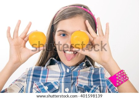 Girl and tangerines. cheerful teen girl holding oranges near the face. Healthy girl with vitamins in the form of citrus fruits - stock photo