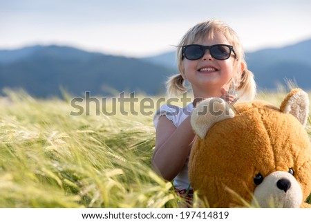 Girl and Teddy bear in a wheat field A little girl playing with teddy bear in a wheat field - stock photo