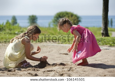 girl and toddler is having fun in the playground - stock photo