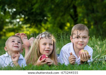 girl and two boys lay on the grass and eat apples