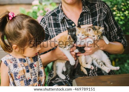 girl and woman playing with kittens.