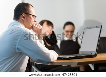Girl and women with men in white shirt with notebook at table - stock photo