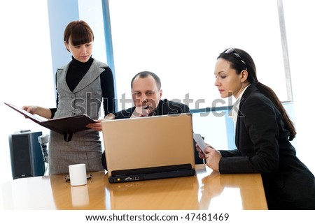 Girl and women with men with notebook at table - stock photo