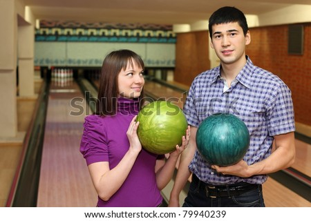 Girl and youth stand with balls for bowling, girl looks at man