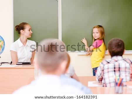 girl answers questions of teachers near a school board - stock photo