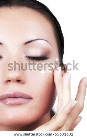 Girl applying cream for eyes area, portrait - stock photo