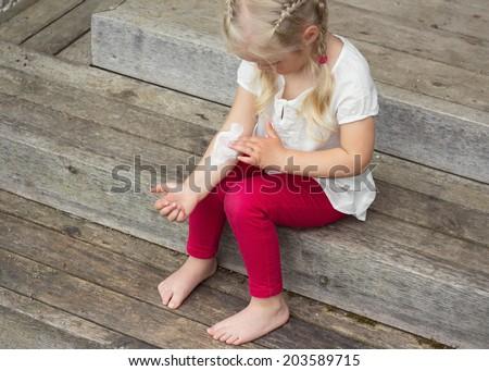 Girl applying cream on allergic skin, eczema treatment - stock photo
