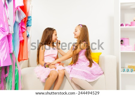 Girl applying make-up on her friend while sitting - stock photo