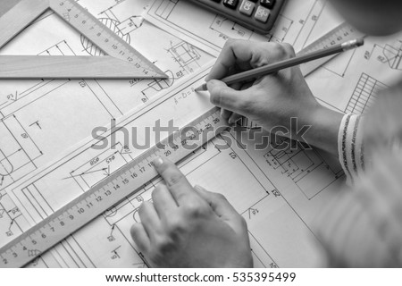 Girl architect draws a plan, graph, design, geometric shapes by pencil on large sheet of paper at office desk.