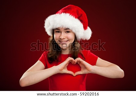 Girl as Santa Claus showing heart shape on red background - stock photo