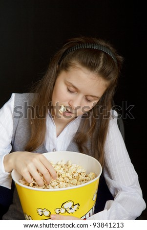 girl asleep in a movie theater with popcorn - stock photo