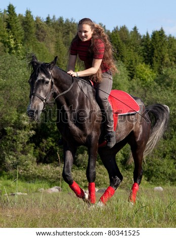 Girl astride a horse galloping on a background of green wood - stock photo