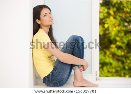 Girl at home. Beautiful young woman sitting on the windowsill and looking away - stock photo