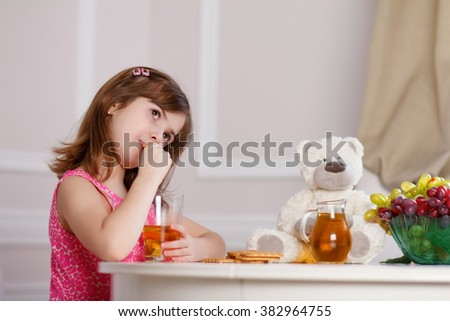 girl at home in the kitchen at the table taking Breakfast, juice and biscuits - stock photo