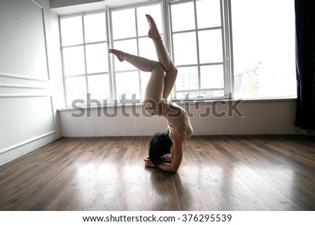 Girl at home practicing and froze in a pose on his hands. Yoga every day.
