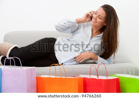 Girl at home talking on mobile with some shopping bags. - stock photo