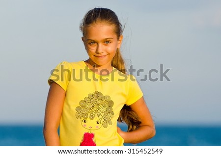 Girl at sunset. beautiful little girl in a yellow T-shirt against the evening sea - stock photo